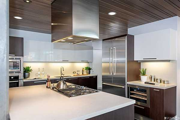 Photo #9 Spectacular chef's kitchen with beautiful Misty Carrera CaesarStone countertops, custom built-in breakfast bar, gorgeous Aran Mia Italian cabinetry, suite of professional appliances by Bosch, Liebherr wine cabinet, and sleek poplar wood panel accent ceiling.