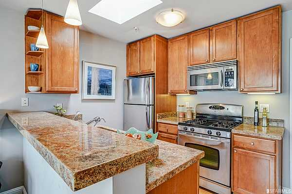 Photo #9 Warm and clean finishes make the kitchen area fun to use and enjoy, whether heating up left overs or pulling together dinner for friends. The skylight overhead brings in natural light all day.