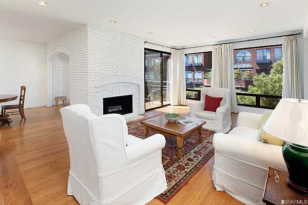Photo #1 Main Floor living room with wood burning fireplace, open to the dining room, and large outdoor view terrace.