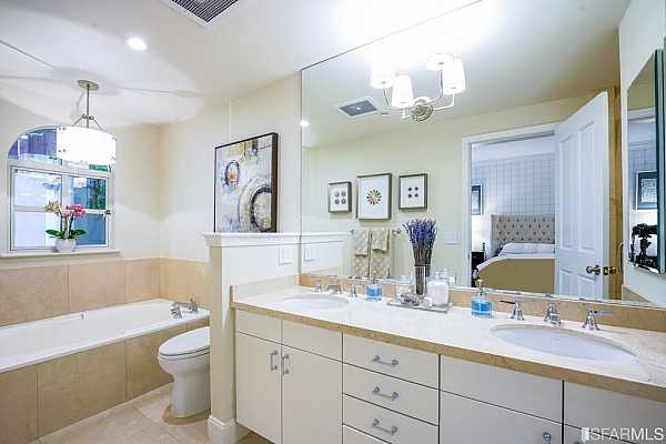 Photo #9 The master bath features a stand alone tun and stall shower.