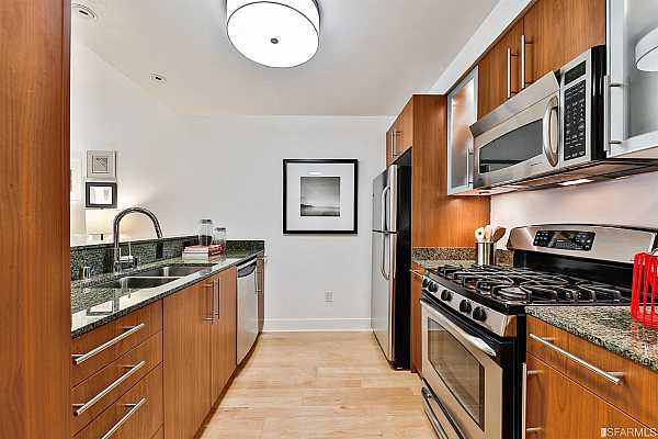 Photo #12 Spacious, chef's kitchen with stainless steel appliances, granite counters, ample Studio Becker custom cabinetry and breakfast bar.