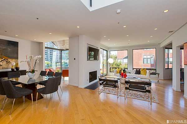 Photo #4 The grand double-height entry foyer with oversized skylight opens to a wonderful bright living room with wood-burning fireplace and large windows opening to a south and west facing terrace with views overlooking Sydney Walton Park, public sculptures and the dramatic downtown skyline