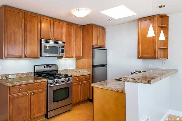Photo #7 Kitchen with granite counters, breakfast bar and stainless steel gas range, microwave, dishwasher and refrigerator