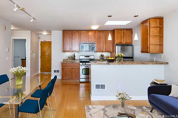 Photo #4 Kitchen with granite counters, breakfast bar and stainless steel gas range, microwave, dishwasher and refrigerator. This image shown with virtual staging.