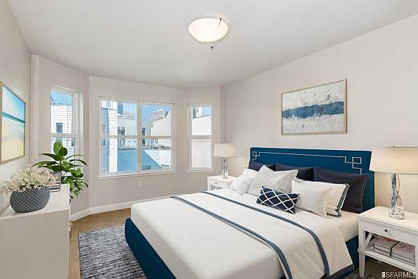 Photo #5 Carpeted bedroom is spacious enough for a king size bed and has views of downtown San Francisco including Salesforce Tower. This image shown with virtual staging.