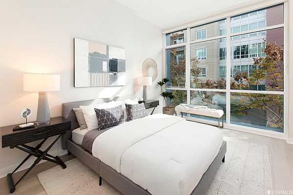 Photo #12 Lower floor master bedroom also has floor-to-ceiling windows and high ceilings.
