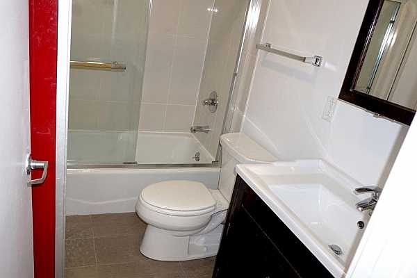 Photo #9 The shower is very nicely tiled and has a sliding glass shower door.