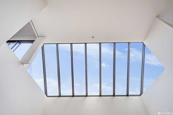 Photo #6 Dramatic skylight above living room provides brilliant natural light tones throughout the day.