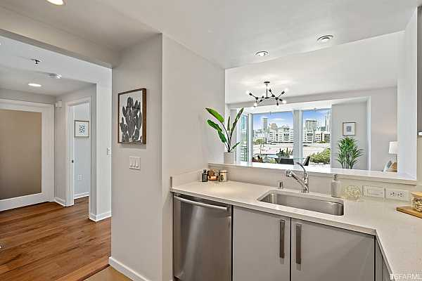Photo #12 Superb high-end kitchen with quartz stone counters, custom Studio Becker cabinetry, stainless sink, tile floors and breakfast island/ pass through open to living/dining. Stainless Bosch appliances include the electric range, oven, hood, microwave oven, dishwasher and refrigerator