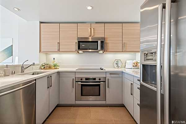 Photo #11 Superb high-end kitchen with quartz stone counters, custom Studio Becker cabinetry, stainless sink, tile floors and breakfast island/ pass through open to living/dining. Stainless Bosch appliances include the electric range, oven, hood, microwave oven, dishwasher and refrigerator