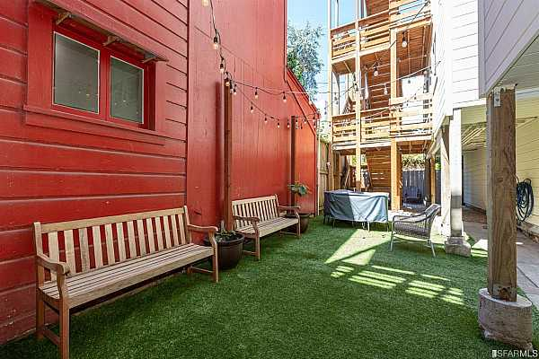 Photo #5 The common area rear yard is completely enclosed and has privacy fencing, bbq area, dining table and benches, and market lighting to create an outdoor entertaining oasis. On this level you have access to your on-site garage parking and huge storage cage.