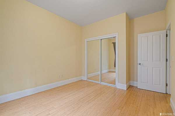 Photo #9 The living area has beautiful crown moldings, tall ceilings, a hardwood floor, and a full-size closet.