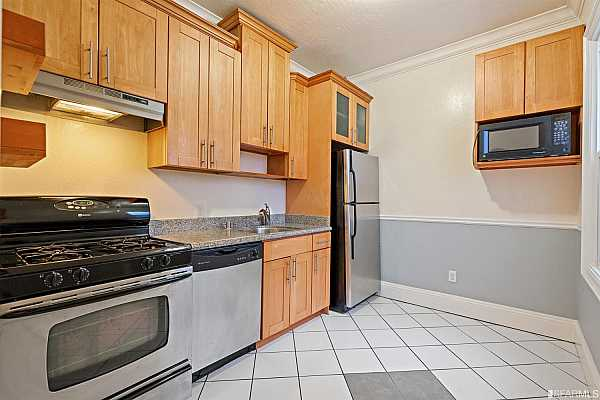 Photo #12 The kitchen has a tiled floor and stainless steel appliances.