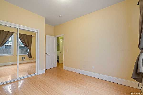 Photo #11 The living area has beautiful crown moldings, tall ceilings, a hardwood floor, and a full-size closet.